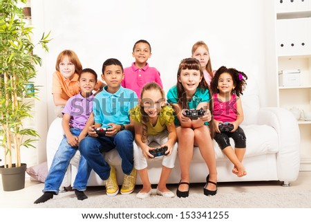 Group of diversity looking kids, boys and girls playing videogame sitting on the sofa holding game controllers - stock photo