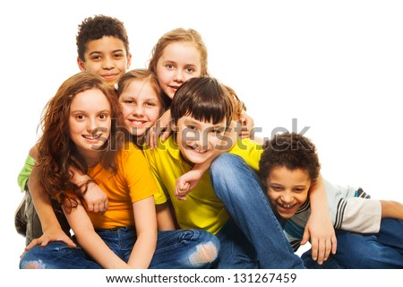 Group of diversity looking kids, boys and girls sitting on the floor hugging and laughing - stock photo