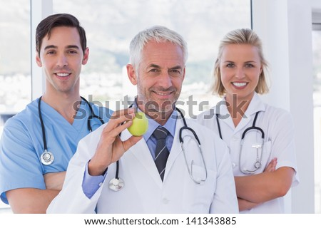 Group of doctor and nurses standing while one is holding a green apple - stock photo