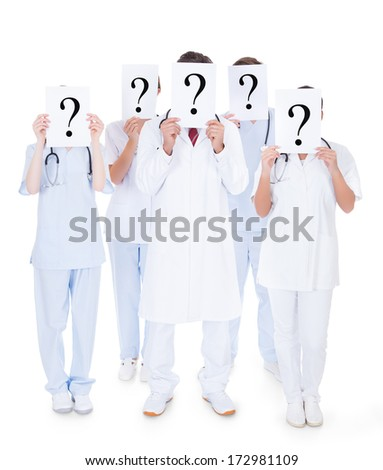 Group Of Doctors Hiding Face With Question Mark Sign Over White Background - stock photo
