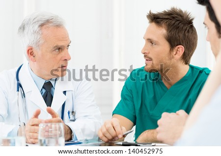 Group Of Doctors Involved In Serious Discussion at Hospital - stock photo