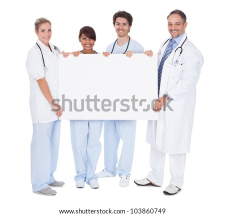 Group of doctors presenting empty board. Isolated on white - stock photo