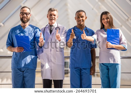 Group of doctors showing thumbs up at the hospital. - stock photo