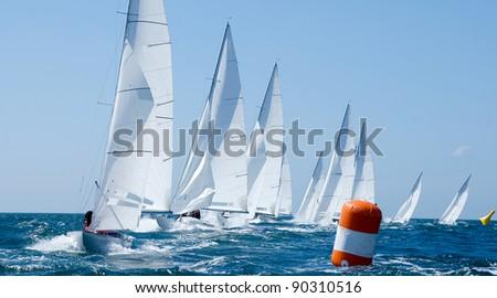 group of dragon yacht sail in regatta near a  buoy - stock photo
