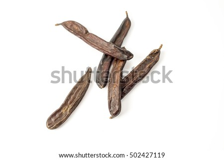 group of dried carob pods whole with seeds, isolated on white background