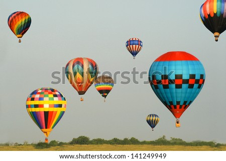 Group of eight colorful balloons in flight with blue sky background.