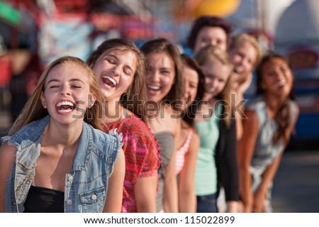Group of eight girls in a row laughing - stock photo