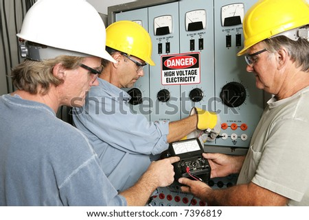 Group of electricians using an OHM meter to test voltage in an industrial power center.  All work being performed according to industry code and safety standards. - stock photo
