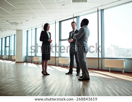 Group of elegant colleagues discussing plans in office - stock photo