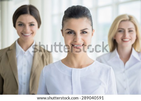 Group of elegant female office workers standing in line and smiling to camera. Successful team concept.