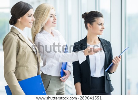 Group of elegant female office workers standing together and looking at something. - stock photo