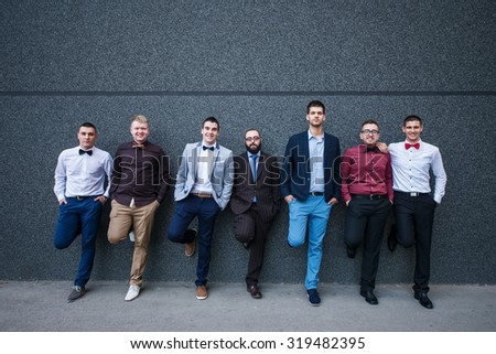 Group of elegant young business people standing against the wall.  - stock photo