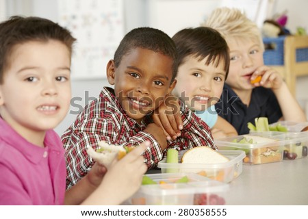 Group Of Elementary Age Schoolchildren Eating Healthy Packed Lunch In Class