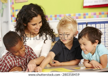 Group Of Elementary Age Schoolchildren In Class With Teacher - stock photo