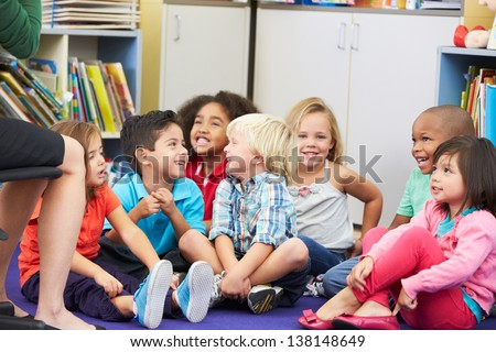 Group of Elementary Pupils In Classroom Listening To Teacher - stock photo