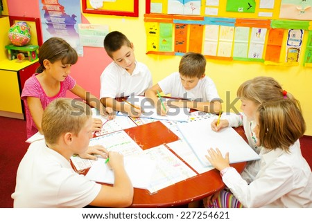 Group of elementary school children sitting around the table in the classroom and reading.  NOTE: All the drawings and artwork in the classroom are made by children. - stock photo