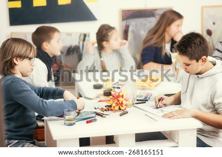 Group of elementary school pupils in classroom on art class - stock photo