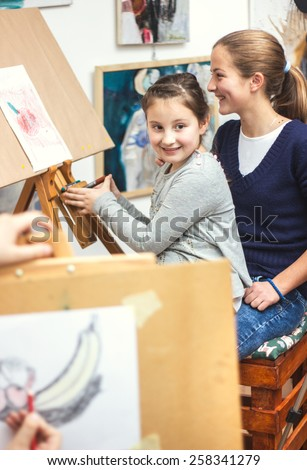 Group of elementary school pupils in classroom on drawing class - stock photo