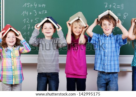 Group of elementary students standing and holding books on their heads - stock photo