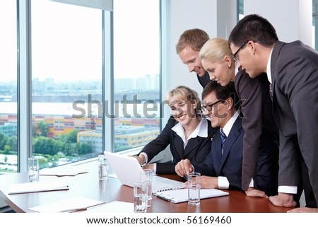 Group of employees in suits at office with the big window - stock photo