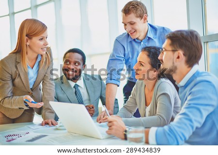 Group of employees looking at confident manager explaining her ideas at meeting - stock photo
