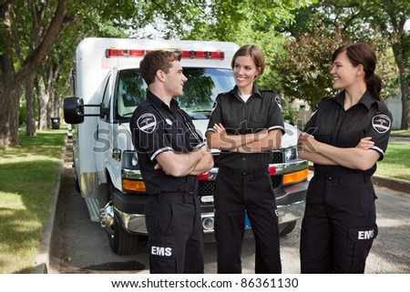 Group of 3 EMS workers standing in front of ambulance visiting - stock photo
