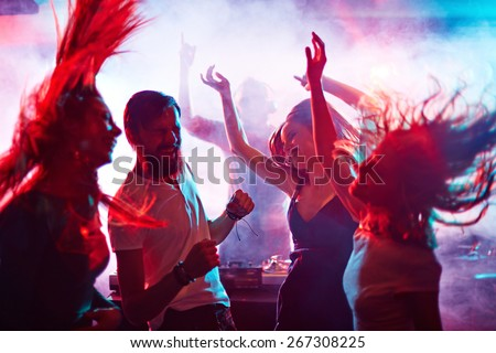 Group of energetic friends dancing in night club