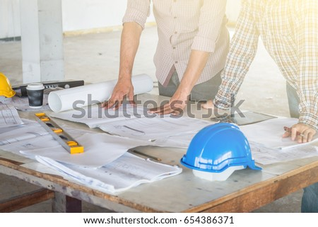 Group engineer checking blueprint on table stock photo 654386371 group of engineer checking the blueprint on the table and talking about construction project with commitment malvernweather Images