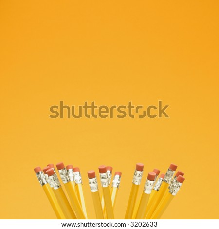 Group of eraser ends of pencils on orange background.