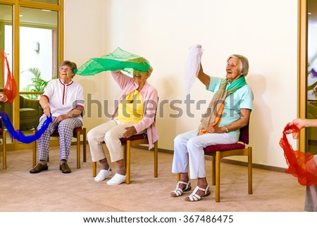 Group of excited senior women seated in chairs waving colorful scarves for physical fitness class indoors - stock photo