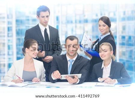 Group of executives discussing while sitting at the table, blue background. Concept of teamwork and cooperation - stock photo