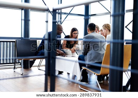 Group of executives sitting and working together using tablets and laptop - stock photo