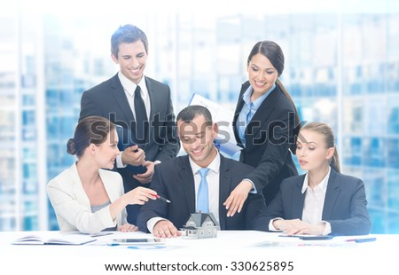 Group of executives working while sitting at the table, blue background. Concept of teamwork and cooperation