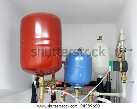 Group of expansion tanks in house boiler room - stock photo