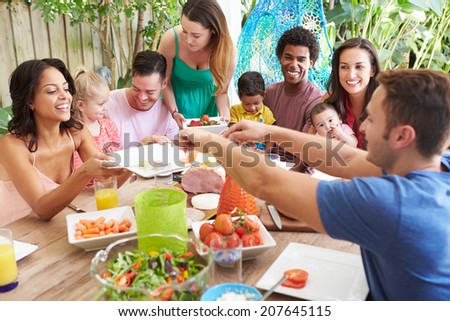 Group Of Families Enjoying Outdoor Meal At Home - stock photo