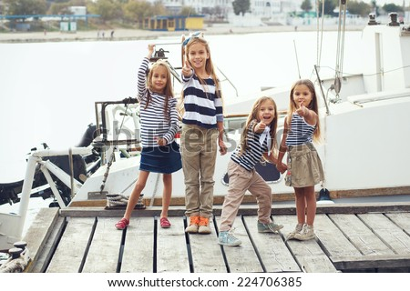 Group of fashion kids sailors wearing navy clothes in marine style enjoying in the sea port - stock photo