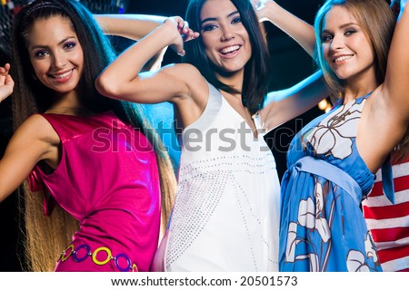 Group of fashionable girls dancing energetically in night club - stock photo