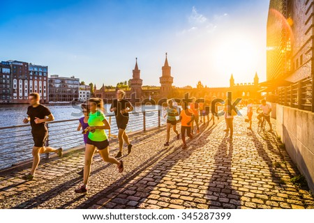Group of female and male young active runners jogging outside in evening light at sunset in summer with retro vintage old Instagram style toned filter and lens flare sunlight effect in the background - stock photo