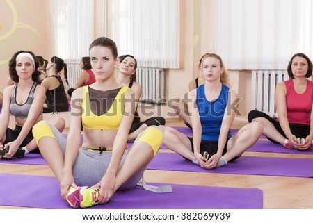 Group of Female Caucasian Sport Athelets Having Indoors Sport Training on Mats. Horizontal Image - stock photo