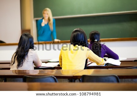 group of female college students in classroom with teacher - stock photo