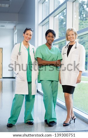 group of female doctors and nurses (Caucasian, African American, Hispanic ethnicity) smiling in lab coats and scrubs, in hospital looking at camera - stock photo