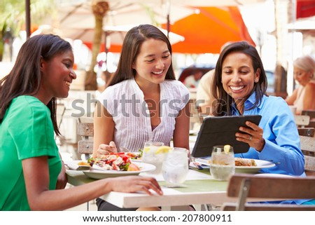 Group Of Female Friends Enjoying Lunch In Outdoor Restaurant - stock photo
