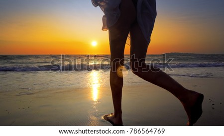 Group of female friends having fun running down the beach at sunset