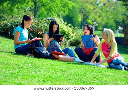 group of female friends learn on green lawn