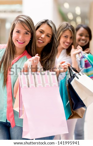Group of female friends shopping holding bags and smiling