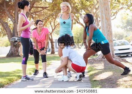 Group Of Female Runners Warming Up Before Run - stock photo