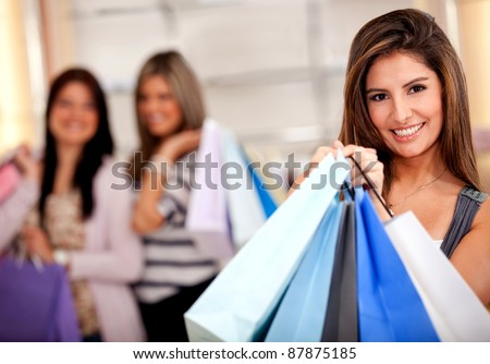 Group of female shoppers holding bags and smiling
