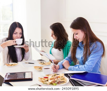 Group of female students studying together at home