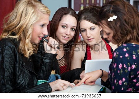 Group of female teen friends reading through a textbook