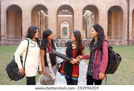 Group of female university students gossiping. - stock photo